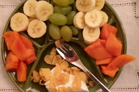 Caki, banana, uva e yogurt con  fiocchi di mais